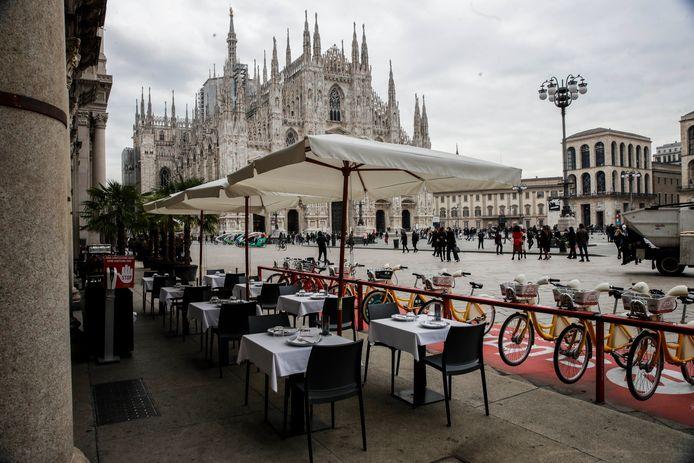 Lege tafels op het plein van de basiliek in Milaan.