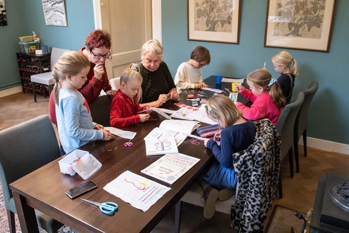 In kleine groepen gaan kinderen in het Bussemakerhuis aan de slag met naald en draad.