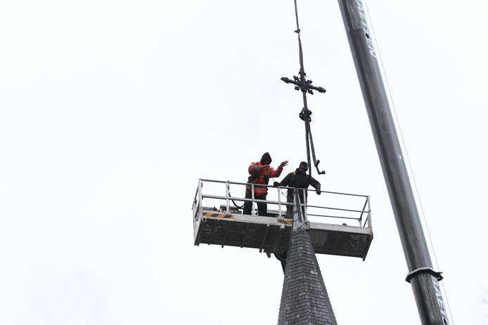 Het kruis wordt van de torenspits van de Christus Koningkerk gehaald.