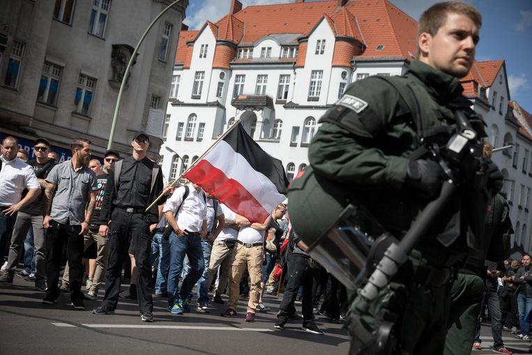 Extreem-rechtse activisten omgeven door veel agenten lopen zaterdag door Berlijn-Spandau. Beeld Christian Mang