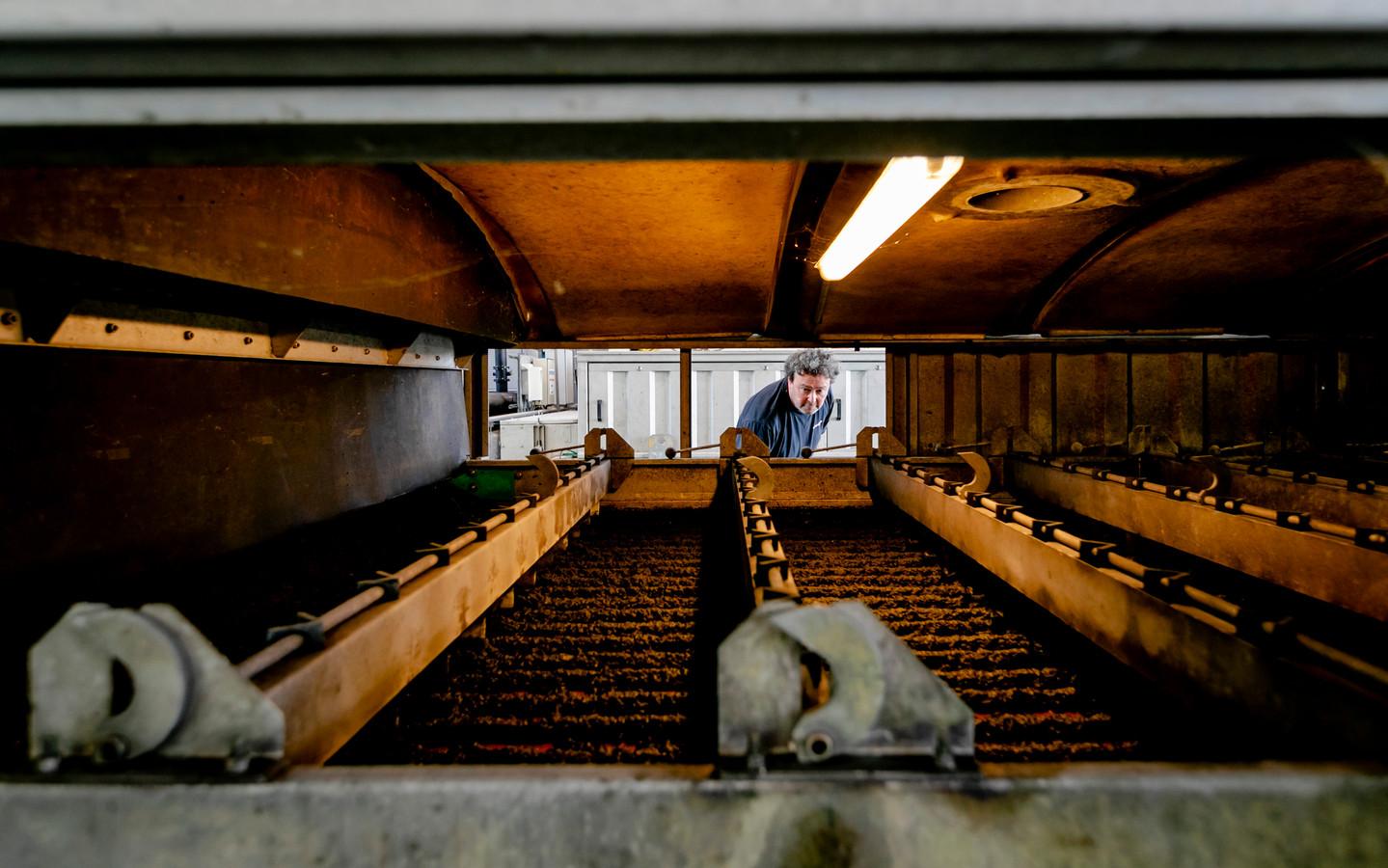Een medewerker van waterschap Amstel, Gooi en Vecht bekijkt de slibverwerking.