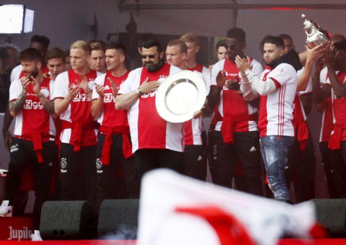 De spelers van Ajax op het podium samen met de vader en broer van Nouri tijdens de huldiging op het Museumplein. A