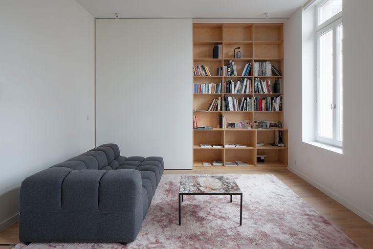 Architectuur en interieur vormen een organisch geheel in dit appartement. Alles werd op plan ontworpen en op maat gemaakt. Achter het schuifpaneel van de boekenkast zit de tv verborgen.   Beeld Johnny Umans
