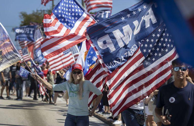 Fans van Donald Trump stonden op 15 februari langs de weg in West Palm Beach in de hoop een glimp van de ex-president op te vangen.  Beeld AFP