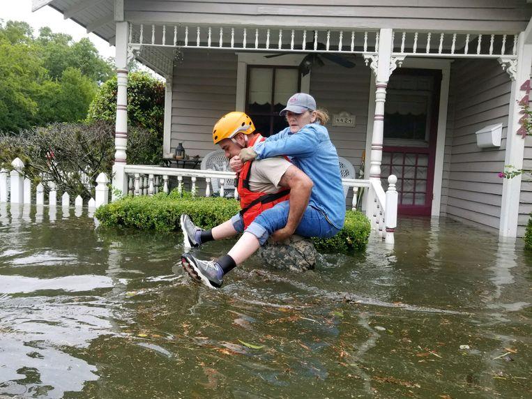 Een lid van de Nationale Garde ontzet een vrouw uit haar huis in de buurt van Houston. Beeld REUTERS