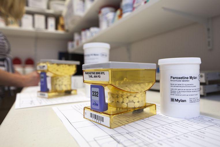 Een apothekersassistente vult de cassettes van een pillenvulautomaat. Op de voorgrond het antidepressivum Paroxetine. Beeld Harry Cock / de Volkskrant