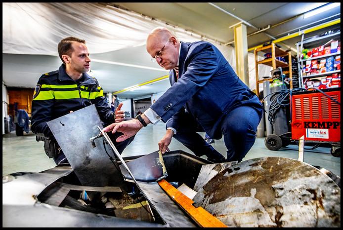 Minister Grapperhaus krijgt uitleg van een agent welke materialen de criminelen gebruikte om de luiken te maken drugs achter te verstoppen