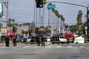 Politie aan de hoek van Fairfax Avenue en Sunset Boulevard. Achter de agenten ligt een lichaam onder een wit laken op de weg, omsloten door politievoertuigen.