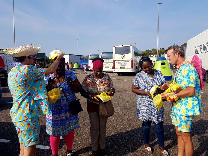 Twee clowneske types delen namens KWF Kankerbestrijding petjes en zonnebrandcrème uit op het parkeerterrein bij Hazeldonk. De organisatie heeft zaterdagochtend vakantiegangers en passanten bewust gemaakt van de gevaren van zonverbranding.