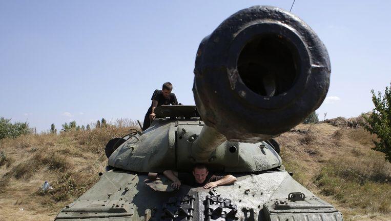 Oekraïense militairen in een WO II Sovjet-tank, ingenomen van separatisten. Beeld afp