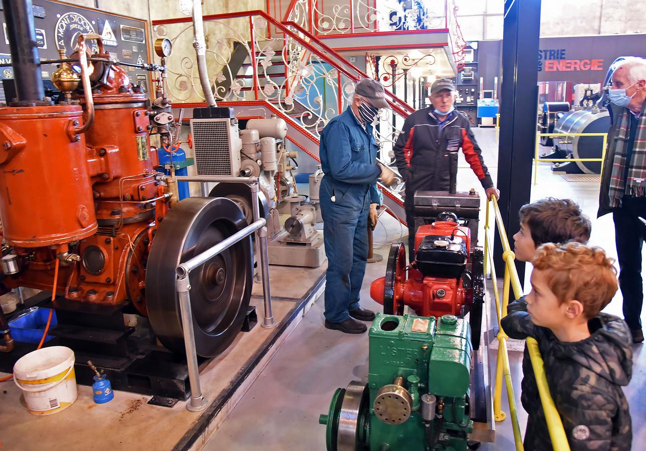 Brent (9) en Jarne (6, vooraan) kijken vol belangstelling voor de draaiende Kromhoutmotor.  Marcel van Campen en Wim Smedeman (l) leggen aan bezoekers uit hoe de motoren werken.
