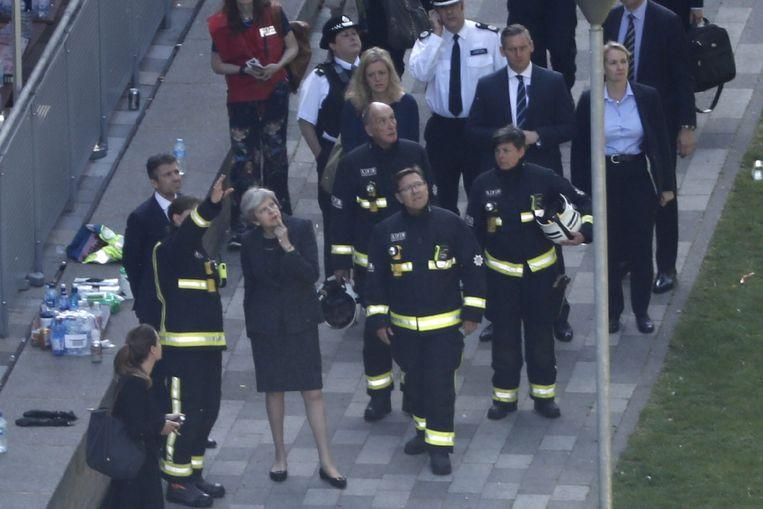 Premier Theresa May praat met brandweerlieden nabij de Grenfell Tower. Beeld AFP