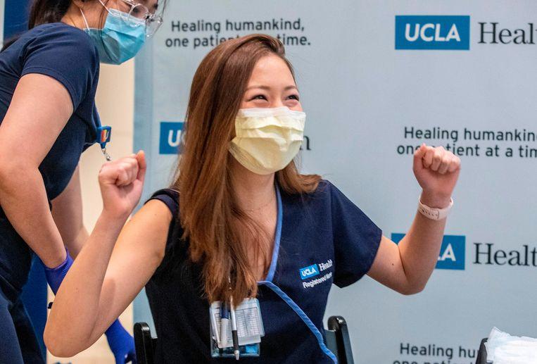 Verpleegkundige Nicole Chang is blij nadat we een van de eerste is om gevaccineerd te worden in het Ronald Reagan UCLA Medical Center in Westwood, Californië.  Beeld AFP