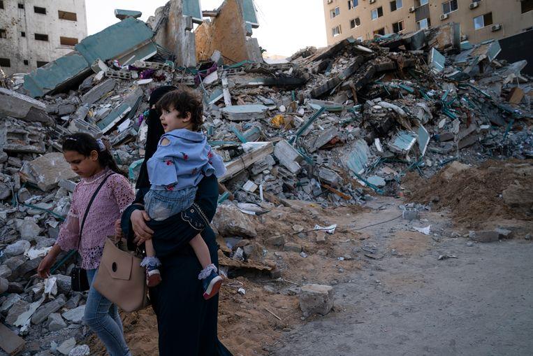 Palestijnen lopen langs de ravage in Gaza. Beeld AP