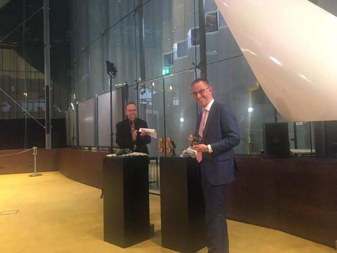 Chris van Koppen (voorgrond) kreeg bij zijn afscheid van Kunstloc de provinciale onderscheiding Hertog Jan van gedeputeerde Wil van Pinxteren.