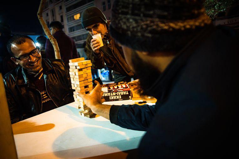 December 2019. Vluchtelingen spelen een spelletje in het centrum van Athene. Een Afghaan: 'Vanavond moet het lukken, Italië bereiken.'     Beeld Nicola Zolin