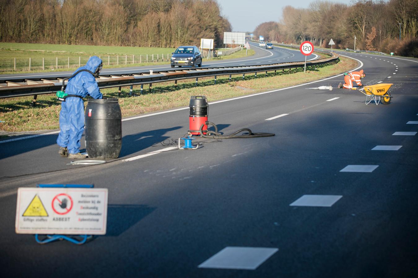 Medewerkers in speciale kleding ruimen het asbest op dat op de A326 bij Nijmegen terecht kwam.