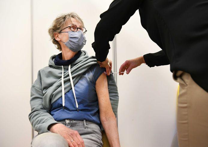 Een huisarts vaccineert een cliënt met het coronavaccin van AstraZeneca.