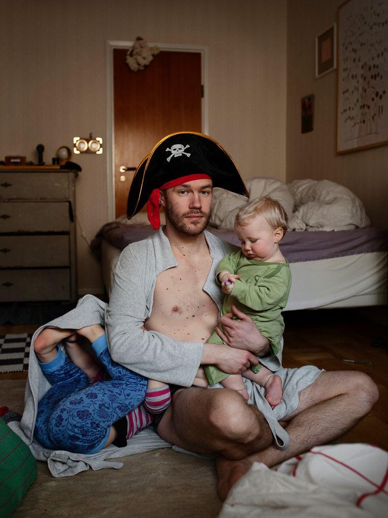 Nils (33), vormgever en Illustrator, met Bibi op zijn arm en Doris. 'Het feit dat ik betaald word om samen met mijn kinderen te zijn, vind ik het toppunt van onze beschaving. Beeld Johan Bävman