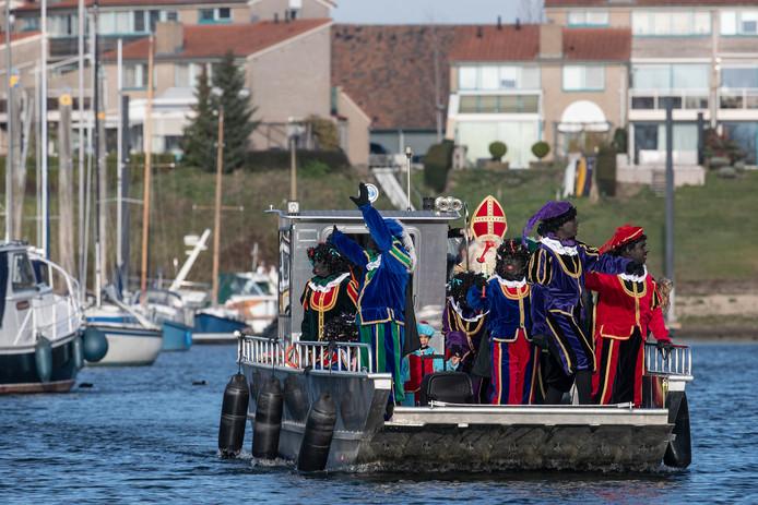 Aankomst Sinterklaas per fietspont in de jachthaven met ondiep water in Giesbeek.