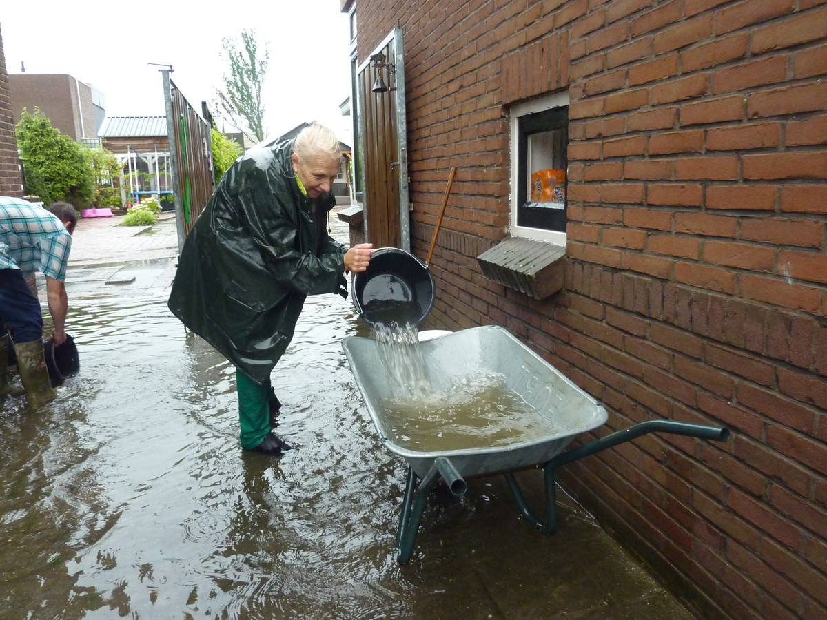 Bewoners van de Nieuweweg in Hardinxveld-Giessendam proberen het water de baas te zijn