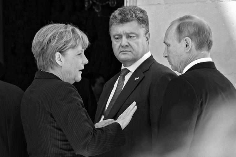 Met de Oekraïense president Petro Porosjenko en de Russische president Vladimir Poetin, juni 2014. (Foto uit het boek Angela Merkel. De kanselier en haar tijd) Beeld picture alliance / dpa