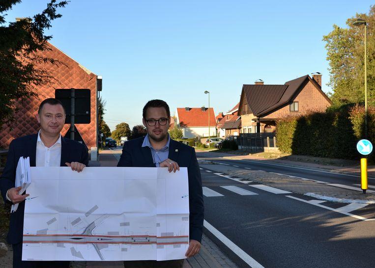 Burgemeester Reekmans en raadslid Vermeulen met de plannen bij de steenweg.