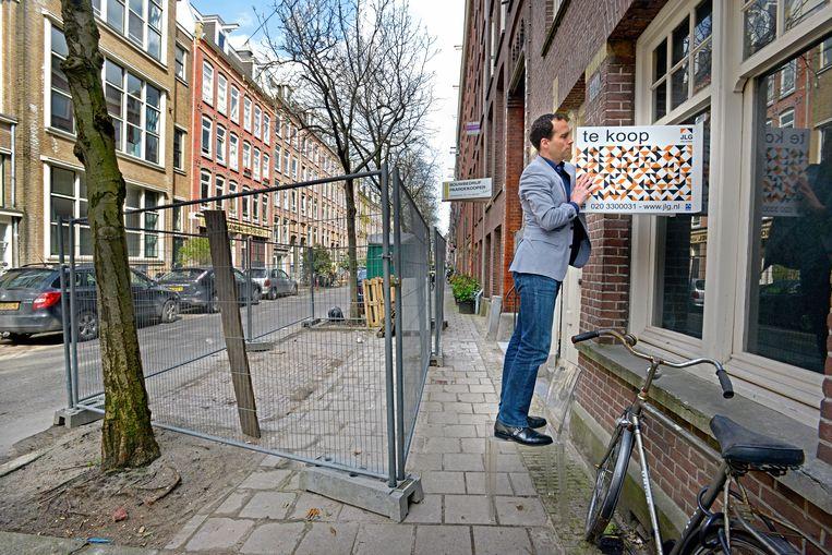 Makelaar Dimitri Jansen plaatst het te koop-bord op een woning aan de Van Ostadestraat 142.   Beeld Raymond Rutting / de Volkskrant