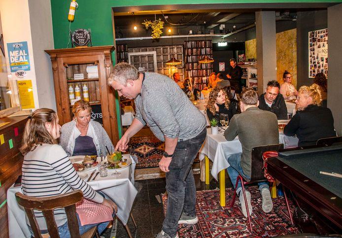Normaal de lobby van Hostel Roots, in de weekenden voortaan een restaurant. Zo werken Hostel Roots en De Burgerij samen om de coronadagen door te komen. Jaap van Corven (gestreept shirt) legt uit wat er wordt gegeten.