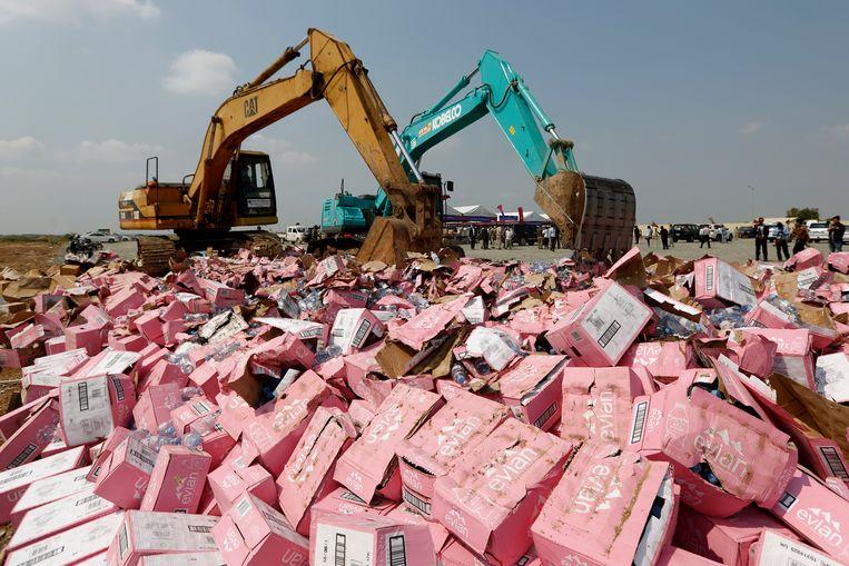 Fake-goederen, waaronder neppe flessen Evian, worden vernietigd in Cambodja na een controle. Archieffoto.