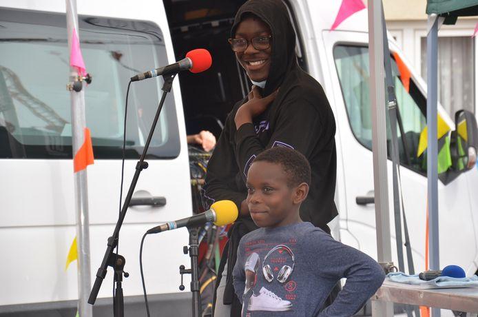 De Blokbusters, een radio- en tv-show voor en door de buurtbewoners van de Pollarewijk. Jonathan (10) met zijn broer Vaneque (19) achter de microfoon.