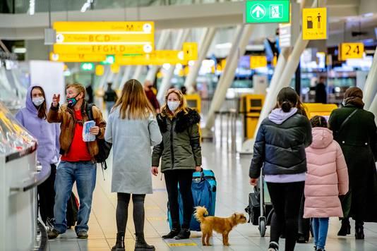 Reizigers op Schiphol. Velen kijken reikhalzend uit naar een vakantie.