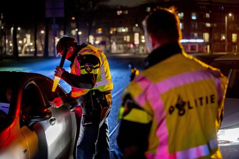De politie controleert een automobilist na het ingaan van de avondklok. Beeld ANP