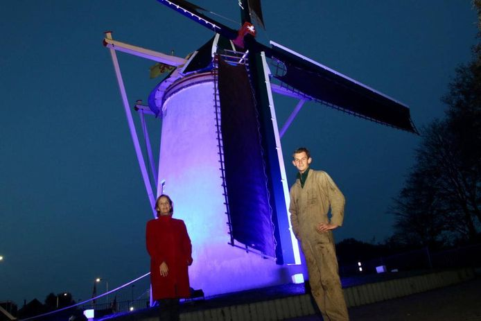 Burgemeester Junius en molenaar Moerland bij de blauw aangelichte molen.