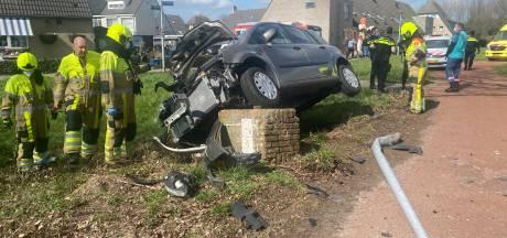 Auto klapt op stenen muurtje en blijft daarop hangen in Tiel