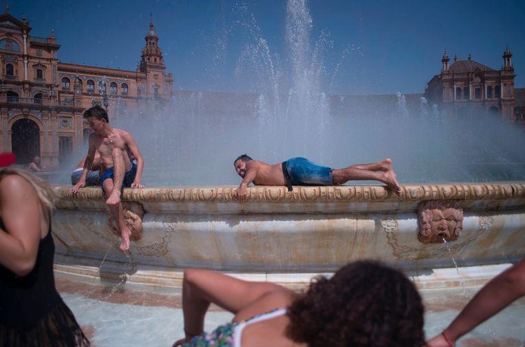 ► Mensen koelen af in een fontein op het Plaza de España in Sevilla. Beeld AFP