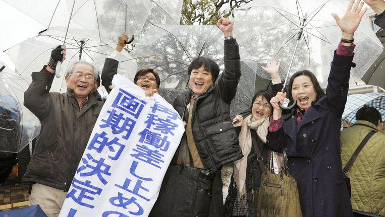 Omwonenden van de reactoren vieren de uitspraak van de rechter. Beeld AP