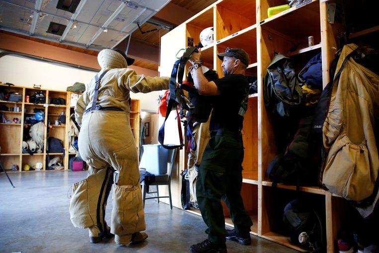 Brandweerman Nate Rose wordt in zijn uitrusting geholpen. Als 'smokejumper' wordt hij vanuit een vliegtuig in een afgelegen natuurgebied gedropt, waar een brand woedt. Zo kan hij als eerste de brand bestrijden. De vliegbasis vanwaaruit hij vertrekt, staat in West Yellowstone, in de Amerikaanse staat Montana.  Beeld Reuters