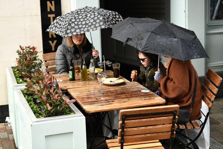 Buiten eten is in Ierland vaak een natte, winderige aangelegenheid. Ook hier in Belfast in Noord-Ierland.  Beeld REUTERS