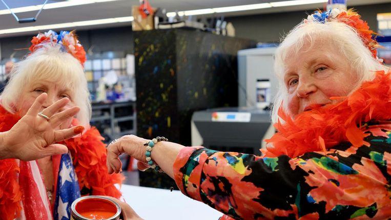 De zussen Louise en Martine Fokkens met het 'hoerenrood'in de verfwinkel. Beeld TON DAMEN