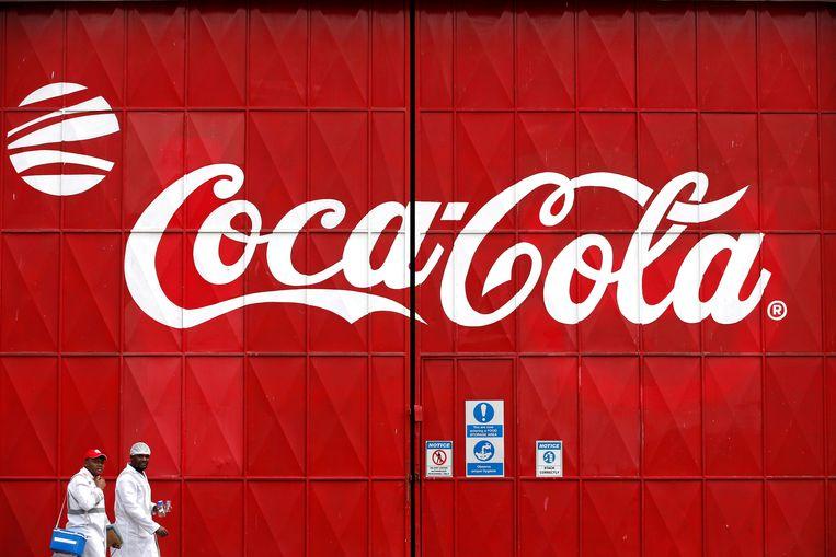 Arbeiders lopen langs een levensgroot Coca-Cola logo, geschilderd op het toegangshek van een Coca-Cola fabriek in Narobi, Kenia. Beeld REUTERS
