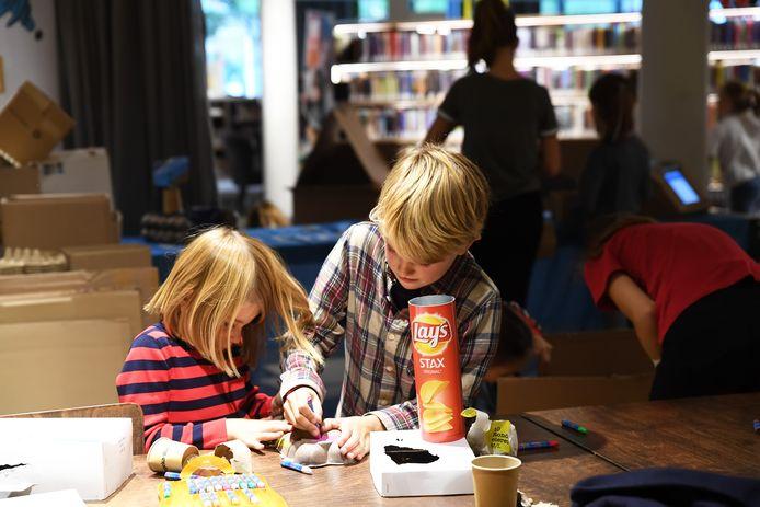 Mees van 7 en Kiki van 4 maken in de bibliotheek een poppenhuis van oude materialen in het kader van de duurzaamheidsweek.