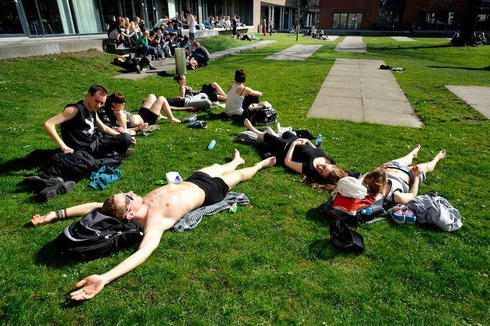 Studenten chillen in de Muzentuin achter de Schouwburg.