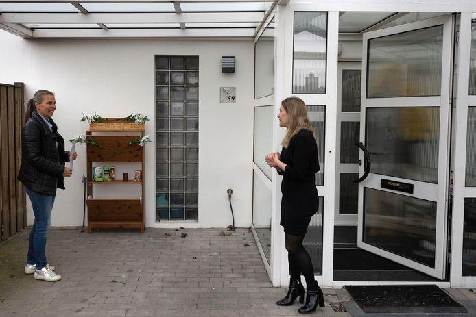 Olga Jonk (l) heeft een verrijdbare foodshare-kast gemaakt.  Ze heeft hem net afgeleverd bij wijkbewoner Sevinç Saygili waar hij voor anderhalve maand onder haar carport staat.