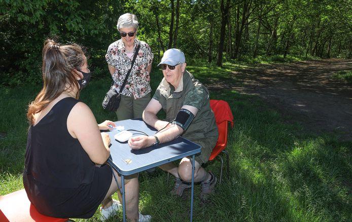 Happy People-gezondheidswandeling door de Clingse bossen, Lisa van Hulst voor Elkaar neemt bloeddruk op van Danny de Loos, zijn vrouw Annemie (midden) kijkt toe.