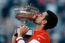 Novak Djokovic kust de beker na zijn overwinning in vijf sets op Stefanos Tsitsipas.