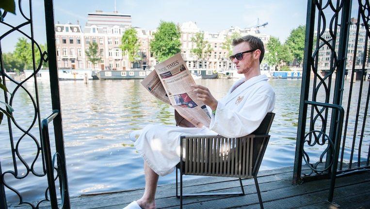 Joep School leest de Financial Times op de steiger van het Amstel Hotel Beeld Mats van Soolingen