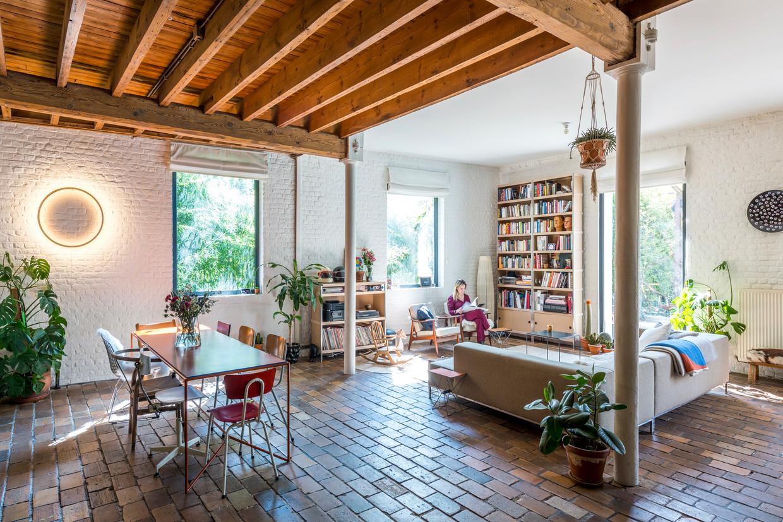 De benedenverdieping is één open ruimte. Zetel en kasten werden neutraal gehouden. De stoelen en  tafel (een ontwerp van Maria) mochten kleurrijker.  Beeld Luc Roymans