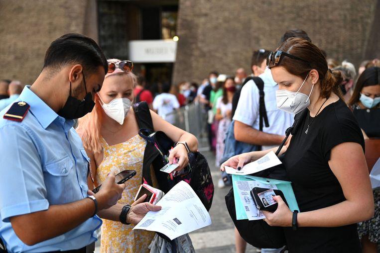 Toeristen bij het Vaticaans museum in Rome laten hun coronavrij-verklaring zien. Beeld AFP