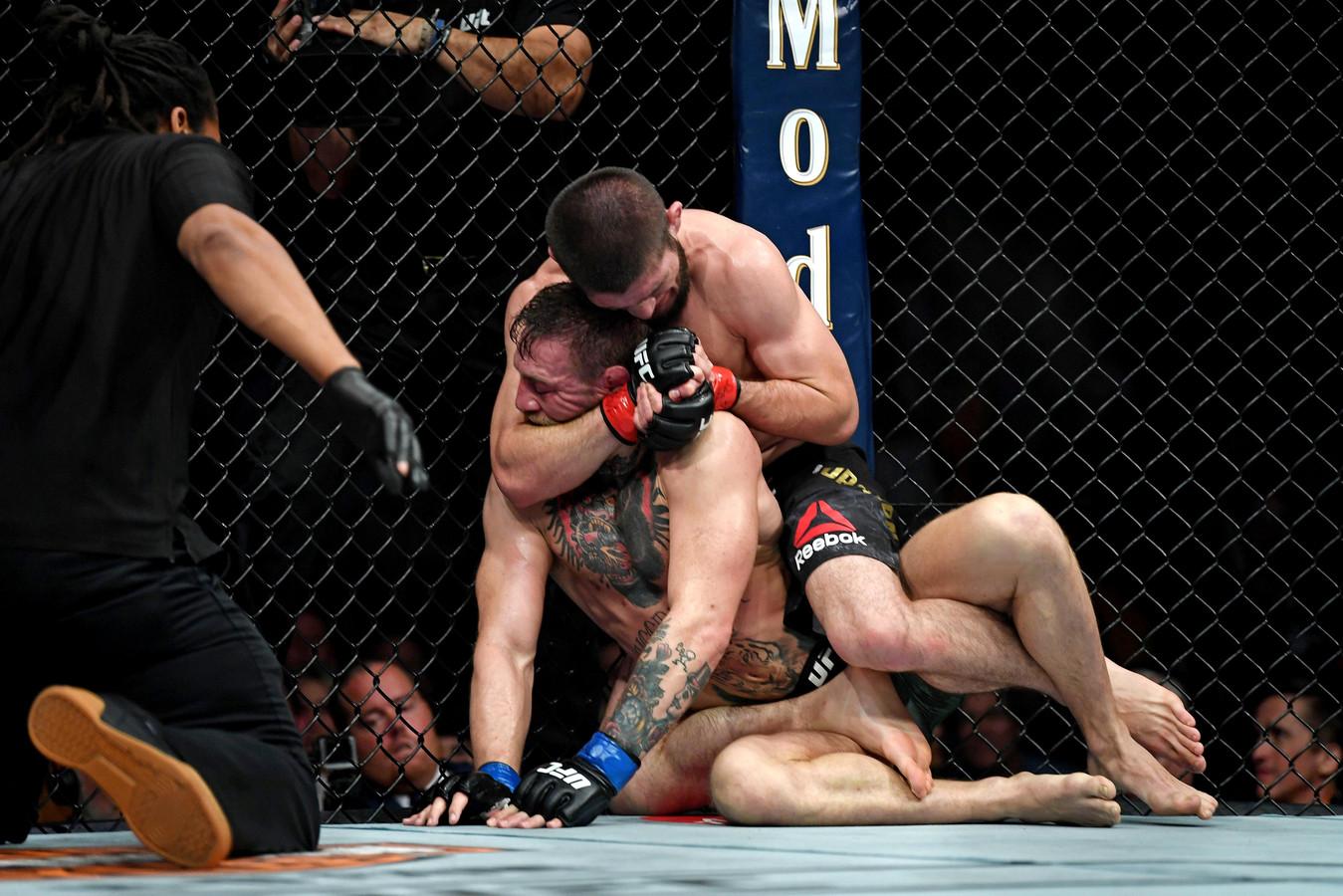 Khabib Nurmagomedov (rode handschoenen) neemt Conor McGregor in een wurggreep tijdens UFC 229 in de T-Mobile Arena.
